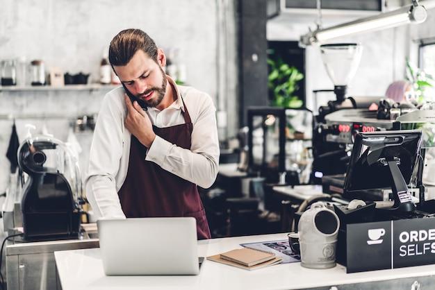 Retrato de bonito barista barbudo homem pequeno empresário trabalhando com computador portátil atrás da barra de balcão em um café