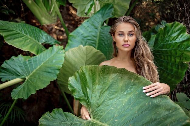 Retrato de bonito caucasiano elegante jovem fêmea com grandes folhas verdes