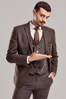 Retrato de bonito e jovem empresário árabe confiante com bigode chique de terno marrom marrom de lã mantém o relógio antigo no estúdio