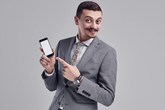 Retrato de bonito e jovem empresário árabe confiante com bigode chique em moda terno completo aponta para o telefone na