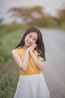 Retrato de bonito feminino asiático olhar para a câmera; a mulher asiática que sorri e olha a câmera ao ar livre.