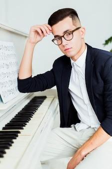 Retrato, de, bonito, homem jovem, sentar-se perto, a, piano, com, musical, folha