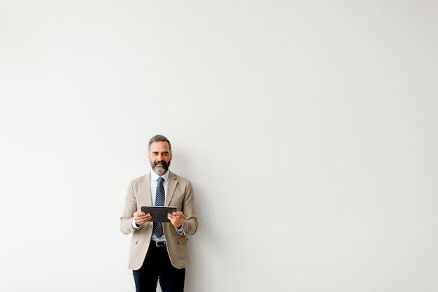 Retrato, de, bonito, homem negócios sênior, com, tabuleta, por, parede