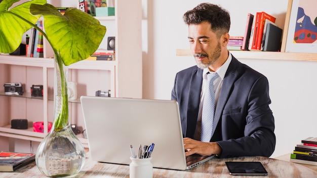 Retrato, de, bonito, homem negócios, usando computador portátil, em, seu, local trabalho