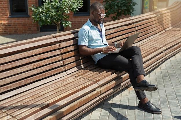 Retrato de bonito jovem africano de óculos com laptop