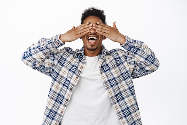 Retrato de bonito jovem afro-americano fechar os olhos com as mãos, sorrindo animado, esperando a incrível festa surpresa, feliz em pé em branco.