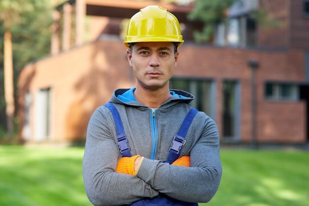 Retrato de bonito jovem engenheiro masculino no capacete, olhando para a câmera, posando ao ar livre enquanto trabalhava na construção da casa de campo. edifício, pessoas, conceito de construção ecologicamente correto