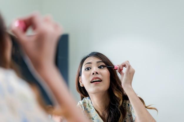 Retrato, de, bonito, jovem, mulher asian, maquilagem aplicando