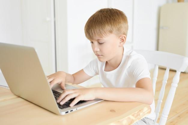 Retrato de bonito menino caucasiano sério em idade escolar, sentado à mesa de madeira usando o computador portátil, mantendo as mãos no teclado. conceito de educação, lazer, pessoas e aparelhos eletrônicos modernos