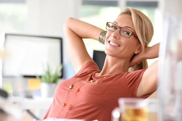 Retrato, de, bonito, middle-aged, mulher relaxando, em, escritório