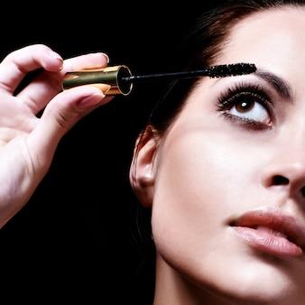 Retrato, de, bonito, mulher jovem, aplicando, mascara, usando, chicote, escova