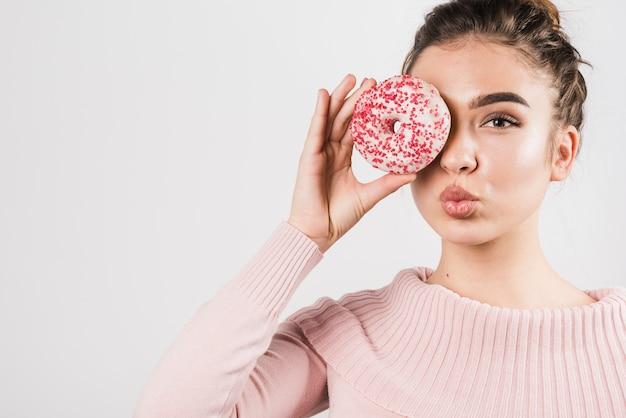 Retrato, de, bonito, mulher jovem, cobertura, dela, olhos, com, donuts