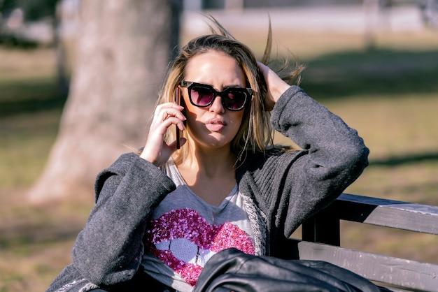 Retrato, de, bonito, mulher jovem, em, urbano, fundo, falando telefone