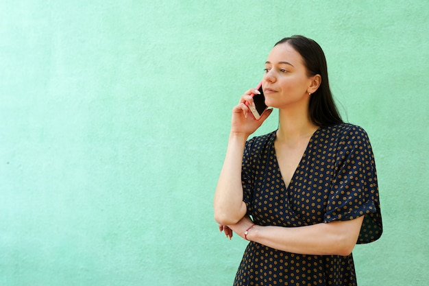 Retrato, de, bonito, mulher jovem, taltking, ligado, telefone, ligado, experiência verde, com, espaço cópia