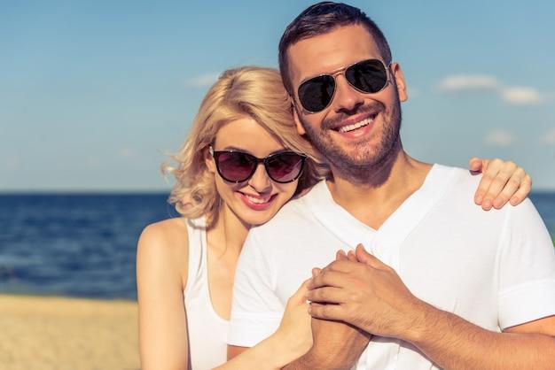 Retrato, de, bonito, par jovem, em, óculos sol, abraçando,