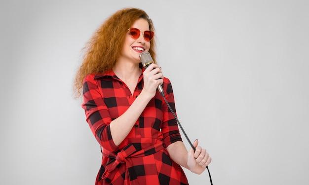 Retrato, de, bonito, ruivo, feliz, mulher jovem, em, óculos de sol, sorrindo, segurando, microfone, ligado, cinzento