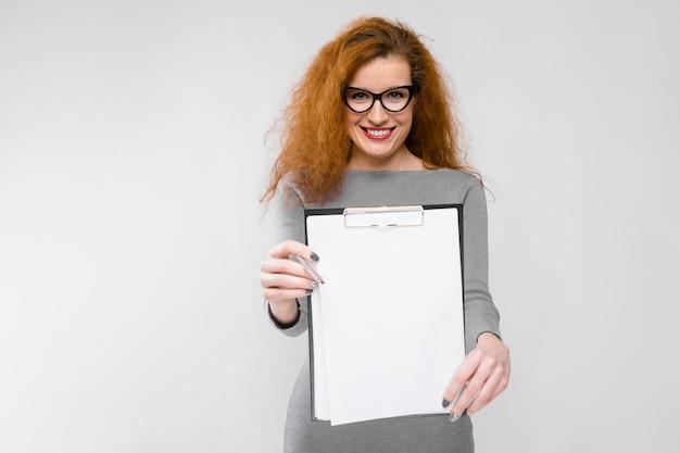 Retrato, de, bonito, ruivo, feliz, sorrindo, jovem, mulher negócio, em, cinzento, roupas, em, óculos, segurando clipboard