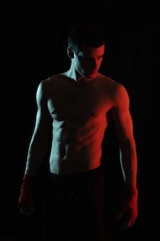 Retrato de boxer masculino posando na luz vermelha e branca