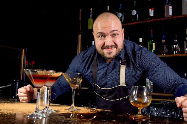 Retrato de braga irritado e estressado com gravata borboleta atrás do bar com bebidas alcoólicas ao redor. estilo de vida estressante do conceito de barista