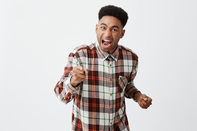 Retrato de bravo cara africana jovem de pele bronzeada, com cabelos cacheados em camisa casual gesticulando com as mãos, gritando com seu amigo, que o traiu e saiu com a namorada.
