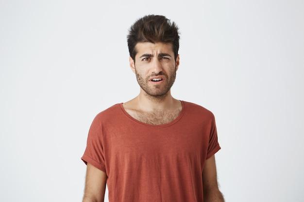 Retrato de bronzeado bonitão com elegante penteado e barba, sendo louco por palavras rudes em sua direção de sua ex-namorada.