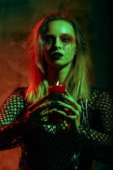 Retrato de bruxa com maquiagem de halloween com uma vela