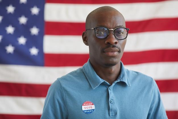 Retrato de cabeça e ombros de um homem afro-americano careca com o adesivo de voto em pé contra a bandeira americana no dia das eleições, copie o espaço