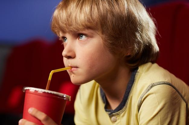 Retrato de cabeça e ombros de um lindo menino loiro bebendo refrigerante enquanto assiste a desenhos animados no cinema, olhando para a tela