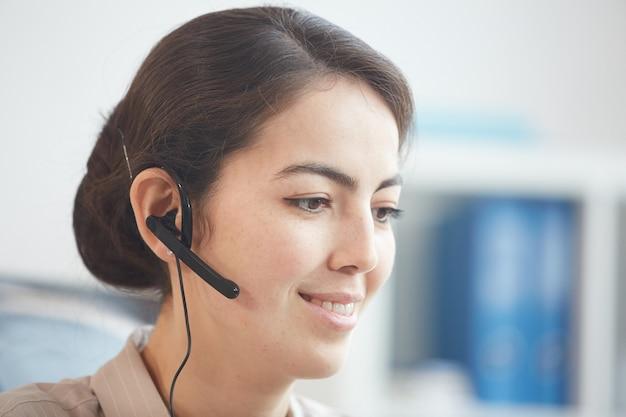 Retrato de cabeça e ombros de uma jovem sorridente usando fone de ouvido e conversando com o cliente enquanto trabalha em uma central de atendimento ou serviço de suporte