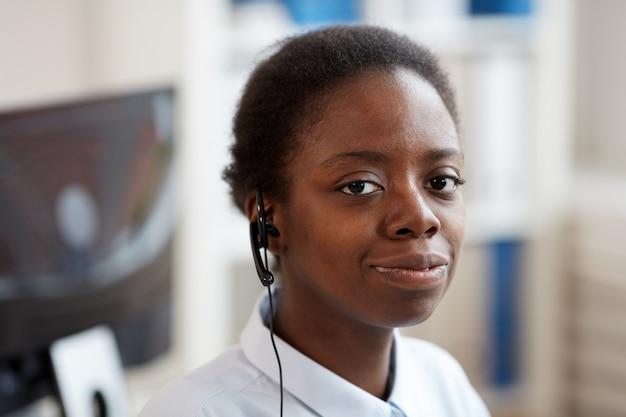 Retrato de cabeça e ombros de uma mulher afro-americana sorridente usando fone de ouvido e olhando enquanto trabalhava em uma central de atendimento de suporte