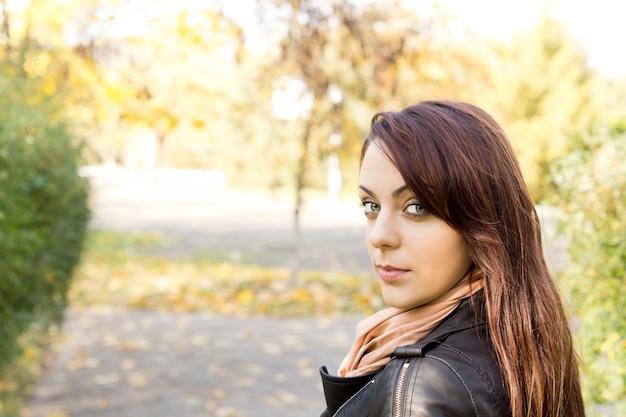Retrato de cabeça e ombros de uma mulher bonita e moderna em pé ao ar livre, olhando para trás