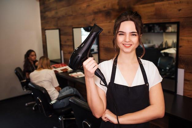 Retrato de cabeleireiro de mulher bonita sorridente, olhando para a câmera