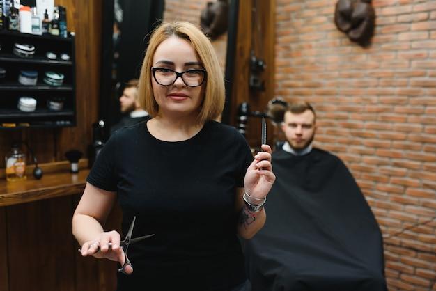 Retrato de cabeleireiro estilista de moda mulher com uma tesoura na mão na barbearia
