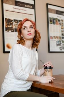 Retrato de cabelo cacheado jovem ruiva caucasiano bonito. jovem sorridente mulher de negócios sentada no café à mesa com uma xícara de café