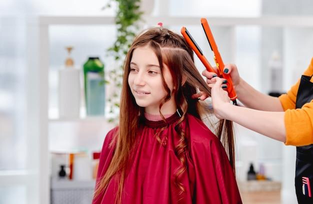 Retrato de cabelo comprido linda jovem modelo com cachos durante o processo de penteado