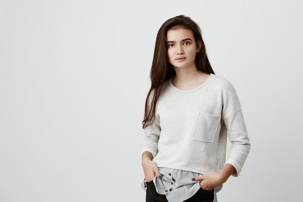 Retrato de cabelo de mulher adolescente bonita com rosto oval, olhos atraentes escuros e cabelo longo e reto, vestido casualmente, sentindo-se relaxado em pé com as mãos nos bolsos, posando dentro de casa