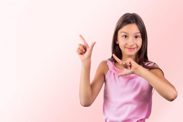 Retrato de cabelo escuro sorridente feliz garota vestindo roupas cor de rosa, apontando para cima com os dedos