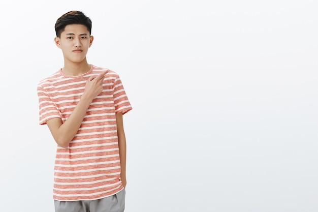 Retrato de calmo e atraente jovem adolescente asiático com penteado curto escuro em uma camiseta listrada, segurando a mão no bolso, apontando para o canto superior direito, enquanto está relaxado e relaxando sobre a parede cinza