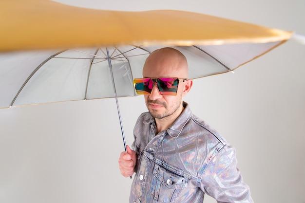 Retrato de camisa elegante caucasiano homem careca e óculos de sol brilhantes detém um guarda-chuva de ouro e prata