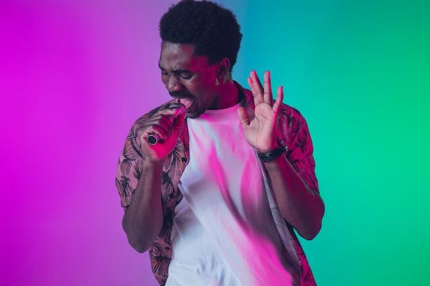 Retrato de cantor afro-americano isolado em fundo gradiente de estúdio em luz de néon