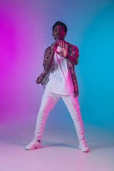 Retrato de cantor afro-americano isolado em gradiente em luz de néon