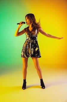 Retrato de cantora caucasiana isolado em fundo gradiente de estúdio em luz de néon