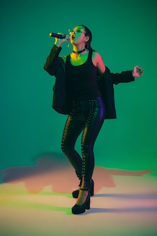 Retrato de cantora caucasiana isolado na parede verde do estúdio