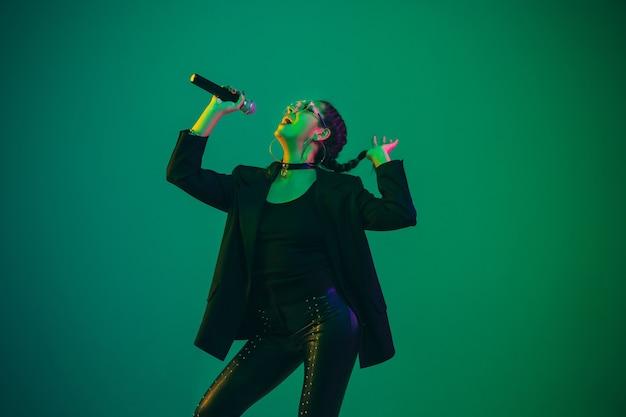 Retrato de cantora caucasiana isolado na parede verde em luz de néon. linda modelo feminino em preto com microfone.