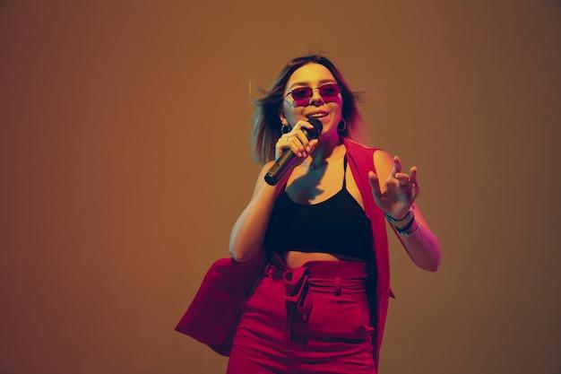 Retrato de cantora caucasiana isolado no estúdio gradiente na luz de neon