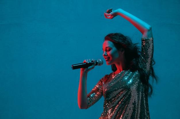 Retrato de cantora isolado na parede azul do estúdio com luz de néon