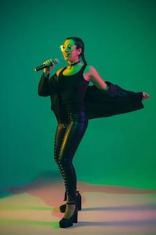 Retrato de cantora isolado na parede verde do estúdio com luz de néon
