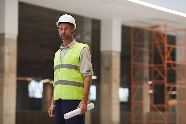 Retrato de capataz maduro usando capacete de segurança e em pé no canteiro de obras,