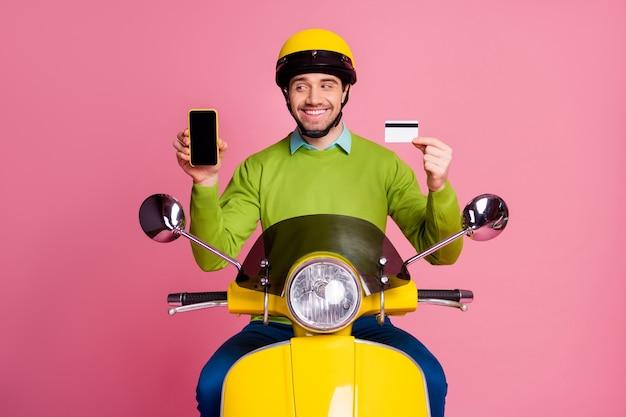 Retrato de cara alegre andando de ciclomotor segurando nas mãos o cartão do banco celular