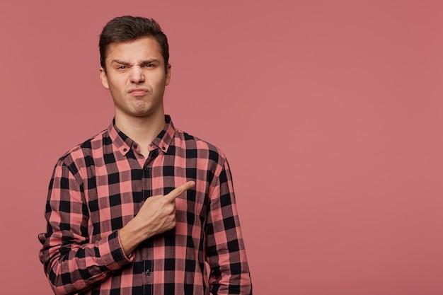 Retrato de cara alegre carrancudo usa camisa quadriculada, olha para a câmera com expressão de nojo, quer voltar sua atenção para copiar o espaço à direita, fica sobre fundo rosa.